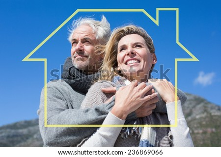 Carefree couple hugging in warm clothing against house outline - stock photo