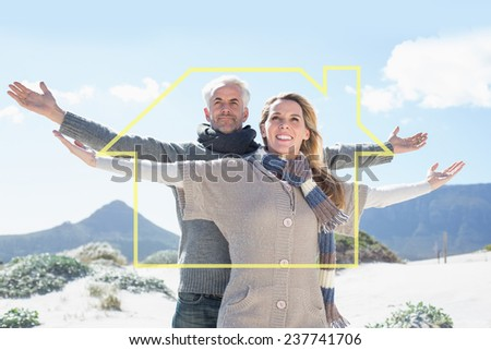 Carefree couple standing on the beach in warm clothing against house outline - stock photo