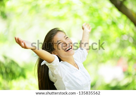 Carefree elated cheering woman in spring or summer forest park full of hope and vitality. Multiracial girl raising her arms up smiling happy. Mixed race Asian Caucasian female model. - stock photo