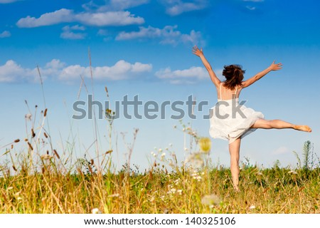 Carefree emotional girl with arms out in field. Summer  - stock photo