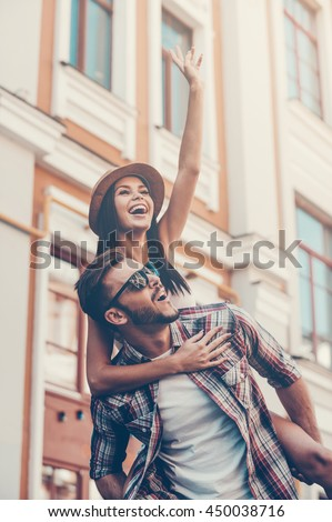 Carefree fun. Happy young man carrying his beautiful girlfriend on shoulders and smiling while walking by the street - stock photo