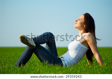 carefree girl sitting at the green field