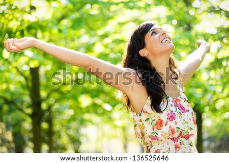 Carefree happy woman in spring or summer forest park raising arms with happiness, hope and vitality. Caucasian girl relaxing and enjoying life on nature outdoors. - stock photo