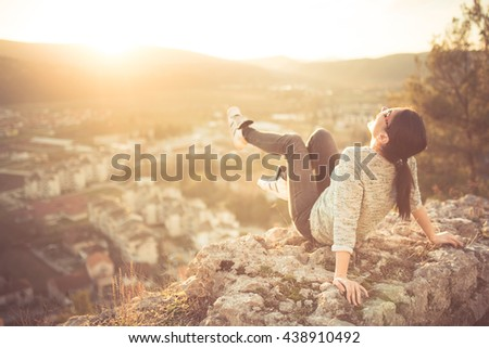 Carefree happy woman sitting on top of mountain edge cliff enjoying sun on her face. Enjoying nature sunset. Resting form daily problems. Freedom.Enjoyment.Relaxing in mountains at sunrise.Daydreaming - stock photo