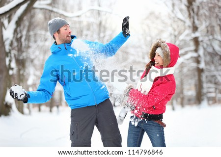 Carefree happy young couple having fun together in snow in winter woodland throwing snowballs at each other during a mock fight - stock photo