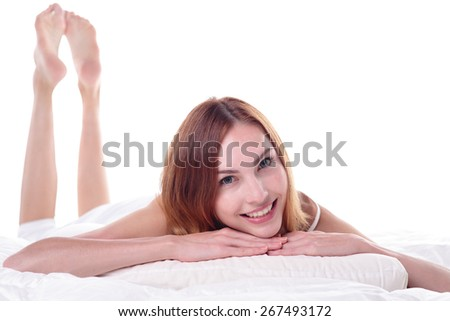 carefree happy young woman smile looking at camera while lying on the bed, isolated on white background , caucasian beauty - stock photo