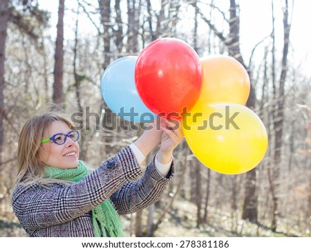 Carefree Lifestyle Happy Young Woman with Colorful Balloons outdoor. Beautiful female enjoyment freedom , winter autumn season. - stock photo