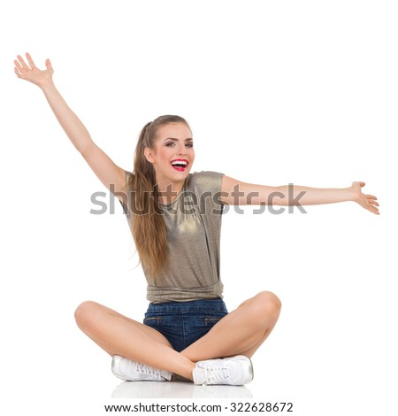 Carefree Sitting Woman. Laughing young woman sitting on a floor with legs crossed and arms outstretched. Full length studio shot isolated on white. - stock photo