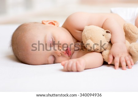 Carefree sleep baby boy with soft toy on bed - stock photo