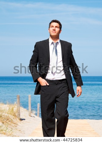 Carefree successful businessman walking with success on boardwalk on coastline with blue sky and sea wearing tie and formal clothes - stock photo