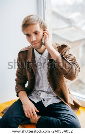Carefree talk. Top view of happy young man talking on the mobile phone and smiling while sitting on the window sill - stock photo