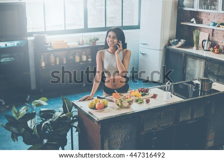 Carefree talk with friend. Top view of young mixed race woman talking on the mobile phone and smiling while preparing food in kitchen