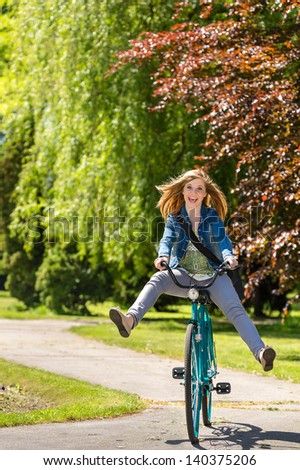 Carefree teenager riding bicycle across the park enjoying fresh air
