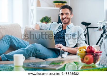 Carefree time at home. Handsome young man working on laptop and smiling while lying on the couch at home  - stock photo