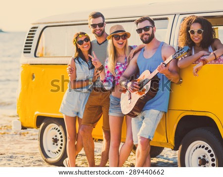 Carefree weekend with friends. Group of young cheerful people bonding to each other and smiling while leaning at their retro styled minivan with sea in the background - stock photo