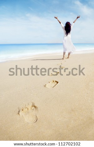 Carefree woman and footprints on the sand. shot at the tropical beach - stock photo