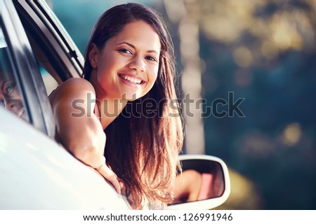 carefree woman driving car on vacation happy smile holiday - stock photo
