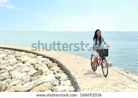 carefree woman having fun and smiling riding bicycle at the beach - stock photo