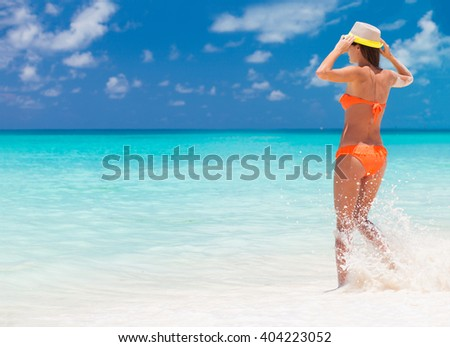 carefree woman having fun at the beach. vacation vitality healthy living concept. water drops - stock photo