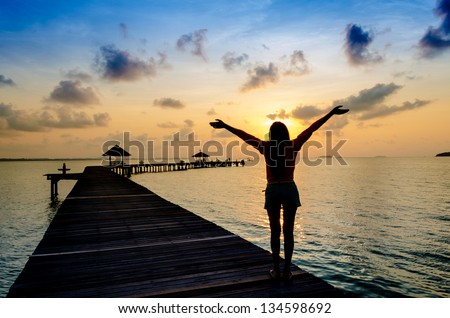 Carefree woman in the sunset on the pier. vacation vitality healthy living concept - stock photo