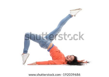 Carefree woman is laying down on the floor. Laughing female lying down on the floor with leg raised. Full length studio shot isolated on white. - stock photo