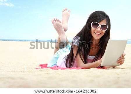 carefree woman uses touchpad tablet on the beach on holiday - stock photo