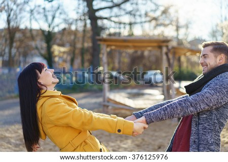 Carefree young couple in love enjoying a date outdoors in an urban environment holding hands and leaning back laughing - stock photo