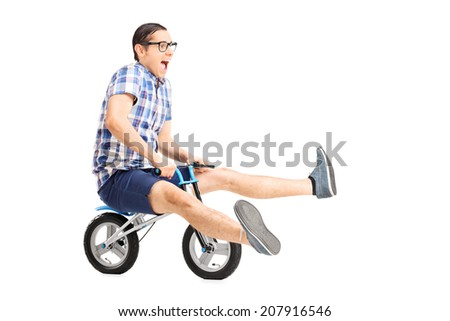 Carefree young guy riding a small bike isolated on white background - stock photo