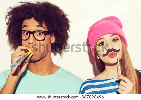 Carefree youth. Funky young couple making faces while standing against white background - stock photo