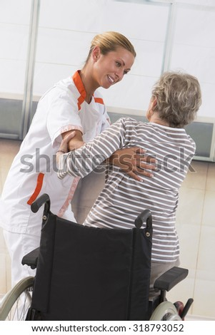 Careful female caregiver helping senior woman to stand up - stock photo