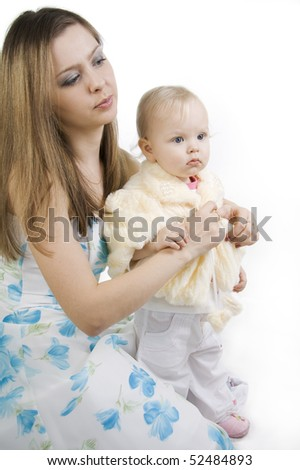 Careful mother dresses the daughter. Isolated on white.