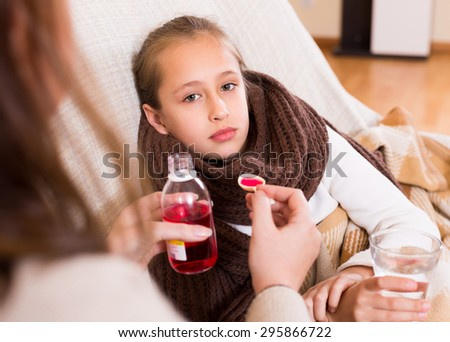 Careful mother giving medicinal sirup to little daughter at home