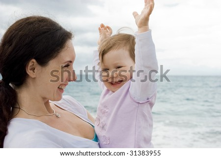 Careful mother holding adorable baby and smiling at her - stock photo