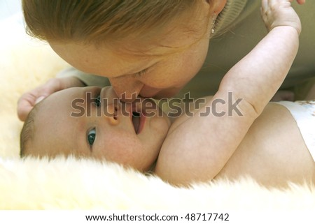 careful mother kisses the charming kid gently - stock photo