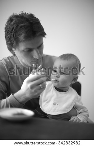 Careful young father feeding his baby - stock photo