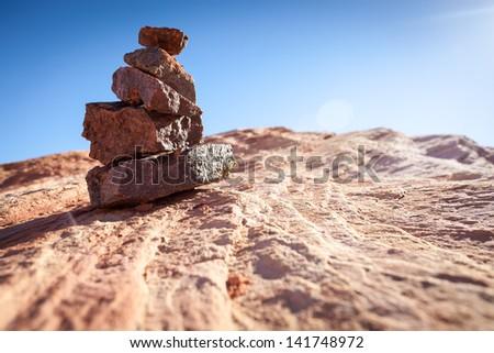 Carefully balanced stack of rocks on slate in the desert sun against the blue sky - stock photo
