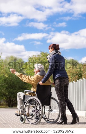 Caregiver and disabled man spending time outdoors - stock photo