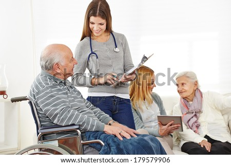 Caregiver doing survey with senior citizens in a nursing home - stock photo