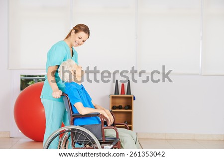 Caregiver dring senior woman in wheelchair to physiotherapy - stock photo