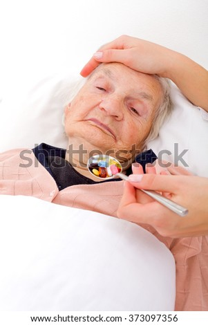 Caregiver giving medication to a senior patient - stock photo
