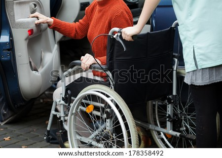 Caregiver helping disabled lady get into the car - stock photo