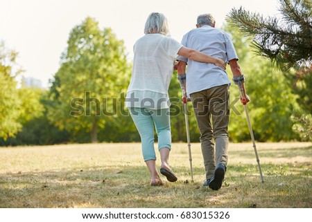 Caregiver helps man walking with crutches in the nature