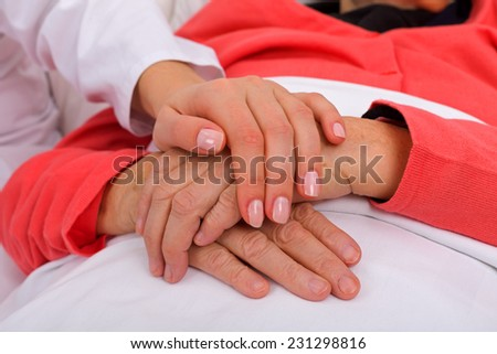 Caregiver holding elderly patients hand at home - stock photo