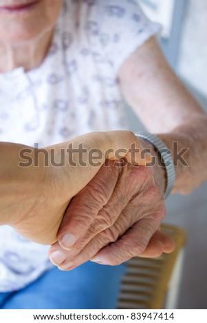 Caregiver holding seniors hand - stock photo