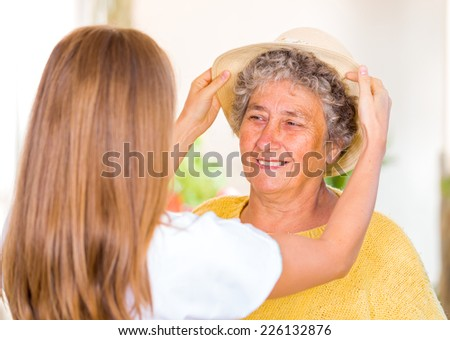 Caregiver put the hat on the happy elderly womans head - stock photo