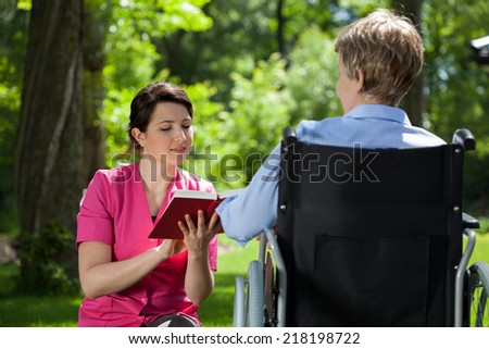 Caregiver reading a book to disabled senior woman outdoors - stock photo