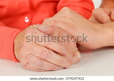 Caregiver touching elderly patients hand at home - stock photo