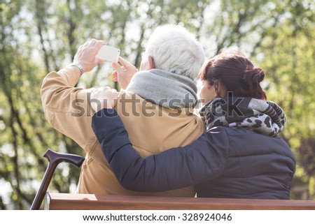 Carer and senior man sitting on the bench - stock photo