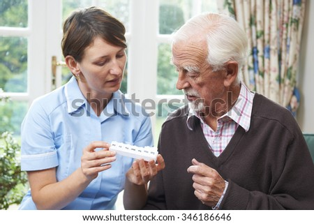 Carer Helping Senior Man With Medication - stock photo