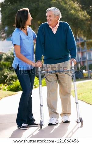Carer Helping Senior Man With Walking Frame - stock photo